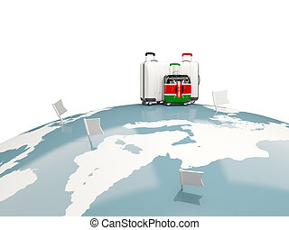 Luggage with flag of kenya. Three bags on top of globe