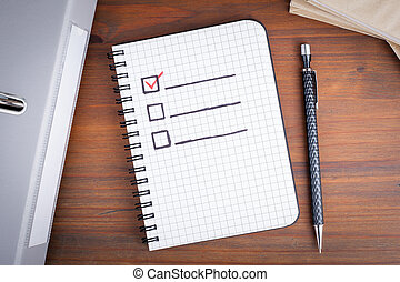 Book with blank checklist on wooden table