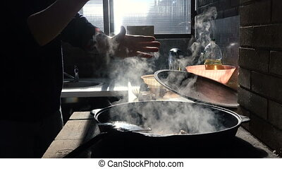 Hands of the cook prepare pilaf in cauldron, add spices, mix...