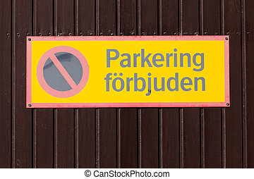 No parking - Faded yellow Swedish no parking sign on brown...