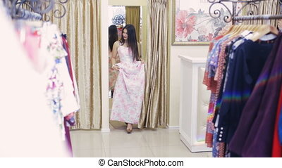 girl in a clothing store trying on a dress in front of a mirror