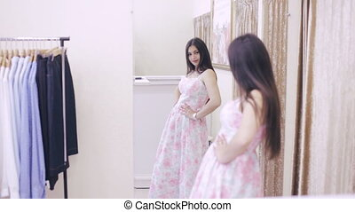 girl trying on a dress in front of a mirror in a store -...