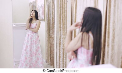 girl trying on a dress in front of a mirror in a store