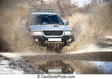Mitsubishi Pajero Sport on dirt road in early spring making...