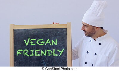 Chef with VEGAN FRIENDLY sign - VEGAN FRIENDLY text with...