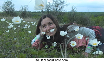 Beauty Girl in the Meadow. Beautiful Young Woman Outdoors. Enjoy Nature. Happy smiling Girl lying on Green Grass with wild Flowers.