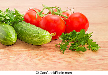 Branch of the red tomatoes, two cucumbers and parsley closeup