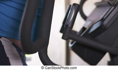 Obese person during exercise on elliptical trainer for...