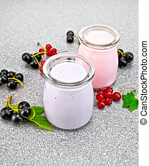 Milk cocktail with black and red currant on granite table -...