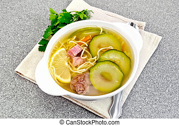 Soup with zucchini and noodles on granite table - Soup with...