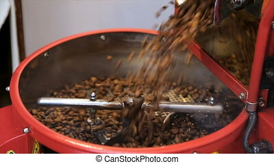 The freshly roasted coffee beans from a coffee roaster being poured into the cooling cylinder.
