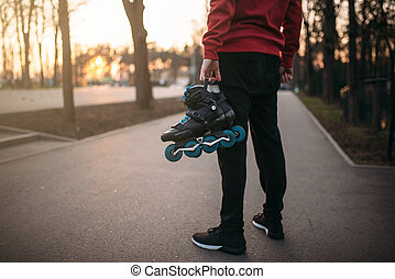 Male person hands with roller skates, city park on...