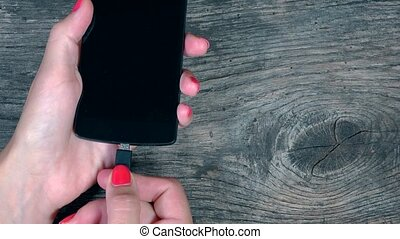 female hand attach smart phones to charger wires