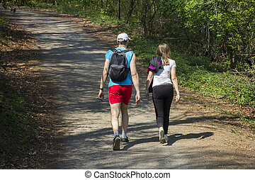 Young woman and a young man walking in the woods