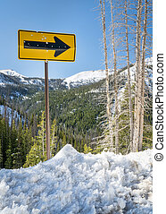 arrow road sign in mountain winter scenery