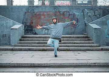 Rap performer posing on the steps, street dancing. Modern...