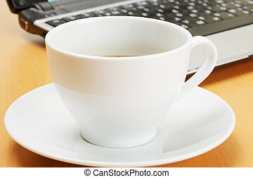 Coffee and laptop - White cup of coffee and laptop on desk...