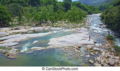 Drone Flies over Rocky Bank River Tourists Stand on Stones -...