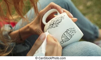 Close-up of female hands drawing a pattern on a white cup. Girl paints ornament sitting on the grass in the evening.