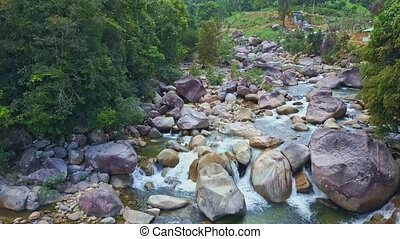 Drone Flies Closely to River Rocky Rapids among Forest -...