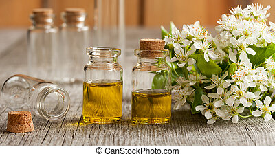 Two bottles of essential oil with white blossoms