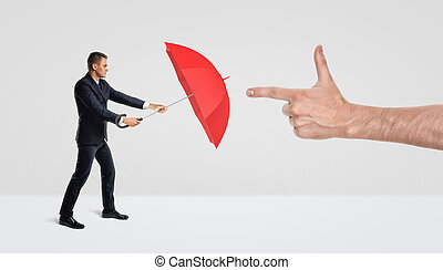 A businessman protecting himself from a giant male hand in a finger gun gesture with a red umbrella.