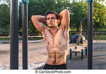 Fitnes man posing on street fitness station showing his...