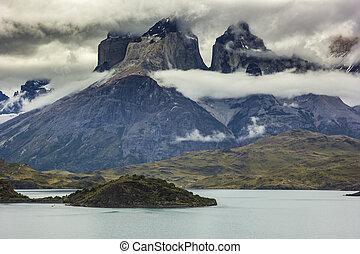 mountains of patagonia in haze at sunrise near blue lake -...