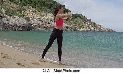 Healthy sporty woman exercising for warming up before running on beach near sea. Female doing turning body exercise.