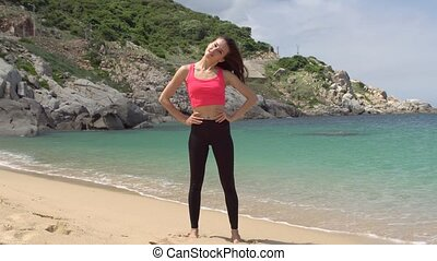 Healthy sporty woman exercising and stretching neck for warming up before running on beach near sea.