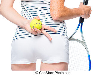 Hands of an athlete with a racket and a ball at the hip level close up