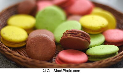 girl takes care of Wicker plates colored macaroon cookies...