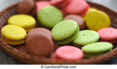 girl puts the French macaroon biscuits in a bowl - close up...