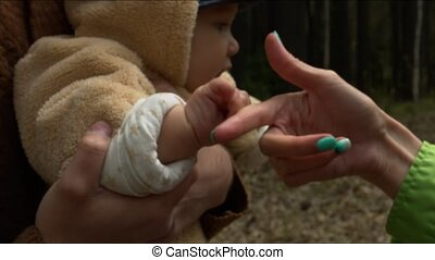 The child holds the mother's hand in the forest.