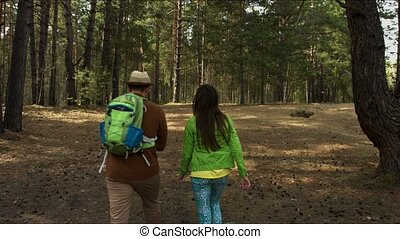 Young family with child walking on path in forest.