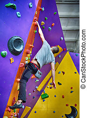 Climber On Artificial Climbing Wall In Bouldering Gym...