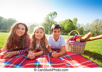 Kids laying on the picnic blanket in summertime