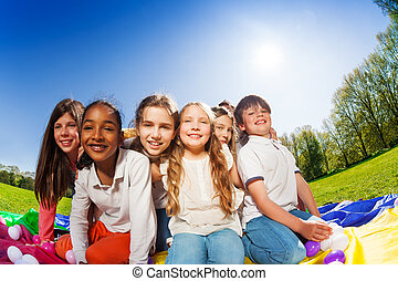 Happy kids sitting on colorful mat in the park