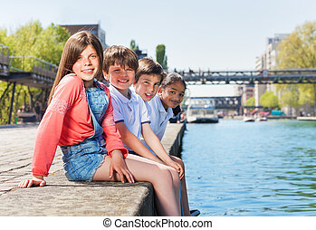 Four happy friends sitting in a line on embankment -...