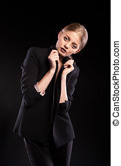 Sexy fashionable woman in suit on black background