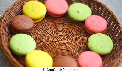girl puts a colored macaroon cookies in a wicker plate close...