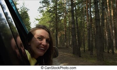 The girl smiles and waves from the car window in the forest.