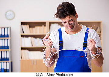Funny young electrician tangled in cables