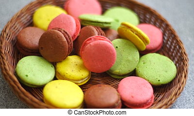 colored macaroon delicious cookies in the wicker plate on a...