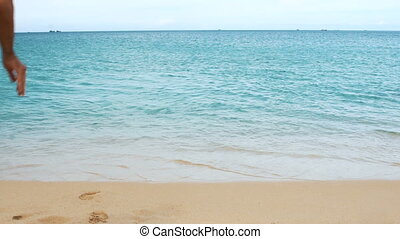 Young man running and jumping into blue sea water, look to camera. Happy boy on beach. Splashes of water. Slow motion