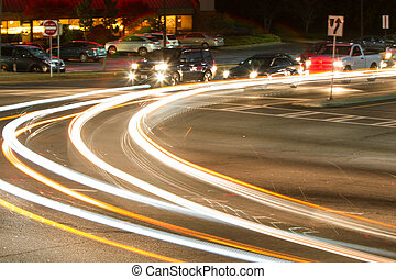 Motion Blur Of Car Headlights Turning At Busy Intersection
