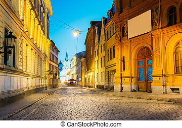 Riga Latvia. Evening View Of Deserted Pils Street, Ancient Architecture In Bright Warm Yellow Illumination