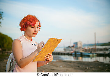 woman with dyed red hair in a pale pink dress with white...