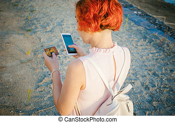 girl with red hair walking by the river at sunset, to make...
