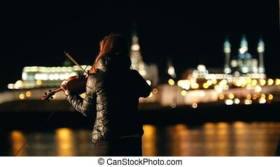 Silhouette of woman violinist playing on violin at night...